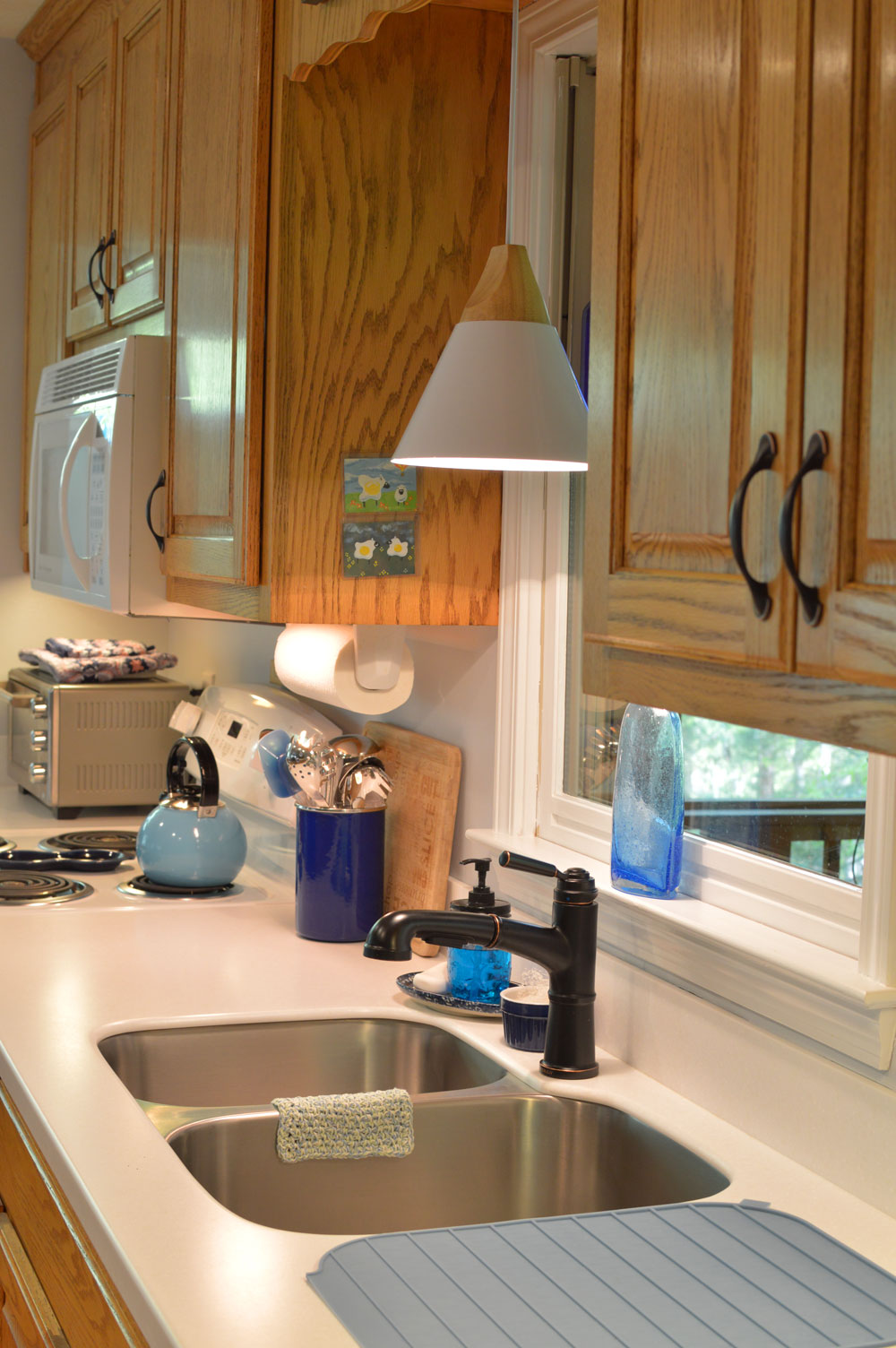 Oak-wood-cabinets-white-countertop-blue-walls-oiled-bronze-fixtures-hardware-kitchen-oak-floors-1