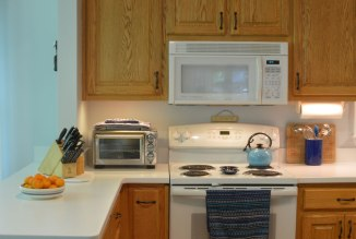 Oak-wood-cabinets-white-countertop-blue-walls-oiled-bronze-fixtures-hardware-kitchen-oak-floors-3